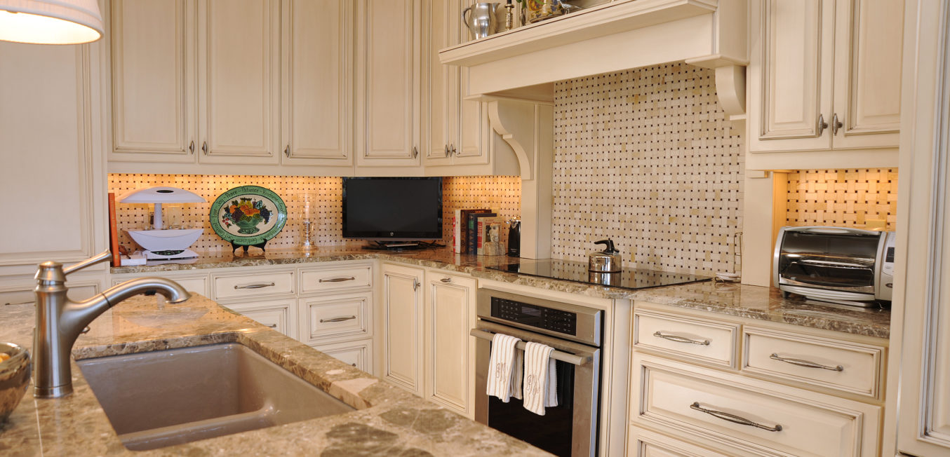 Kitchen with partial overlay cabinetry and recessed panel door fronts