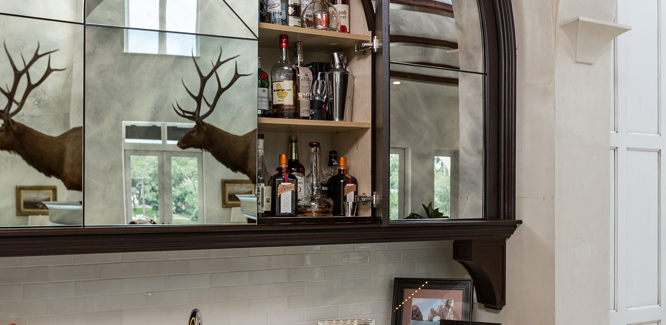 Custom built bar with a dark stained walnut and slab mirror doors