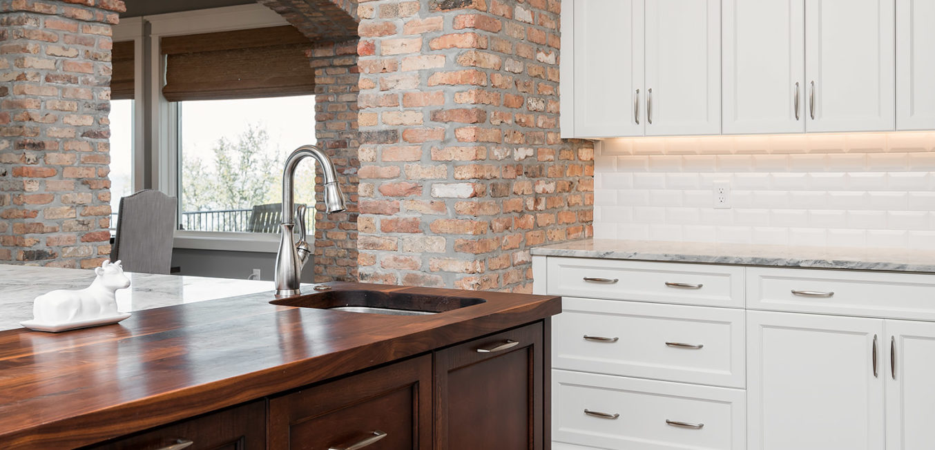 Full Overlay cabinetry with shaker door and drawer fronts. The kitchen island is in a dark stained wood and the side wall cabinets in all white with brick walls.