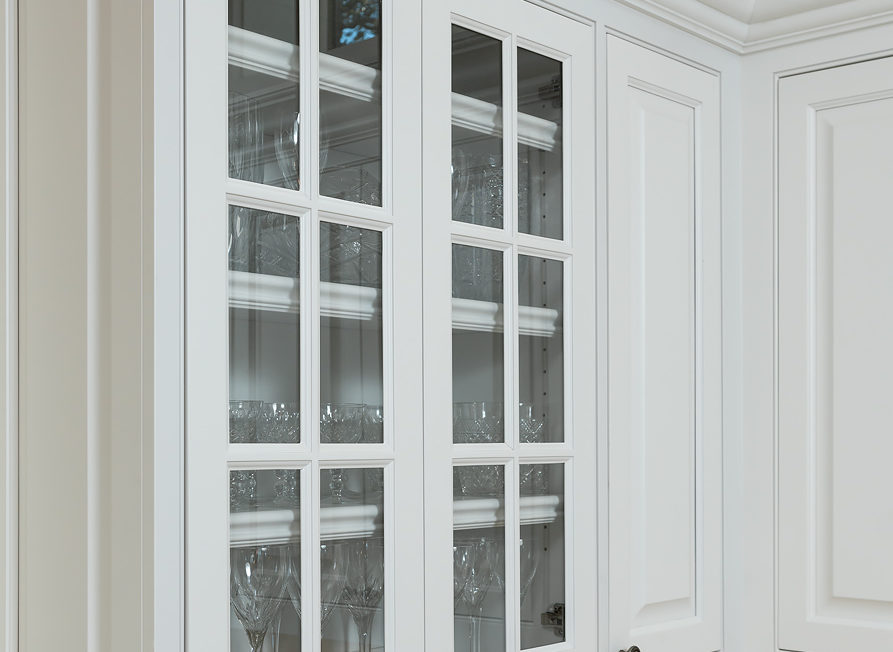 White mullion frame doors inset into upper cabinet row with glass inserts.