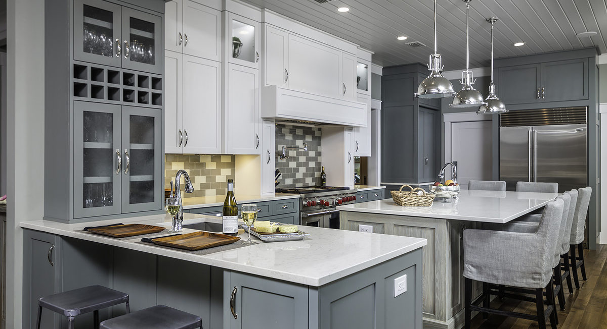 Custom Teal and white kitchen featuring decorative open frame doors with glass inserts as the center panels