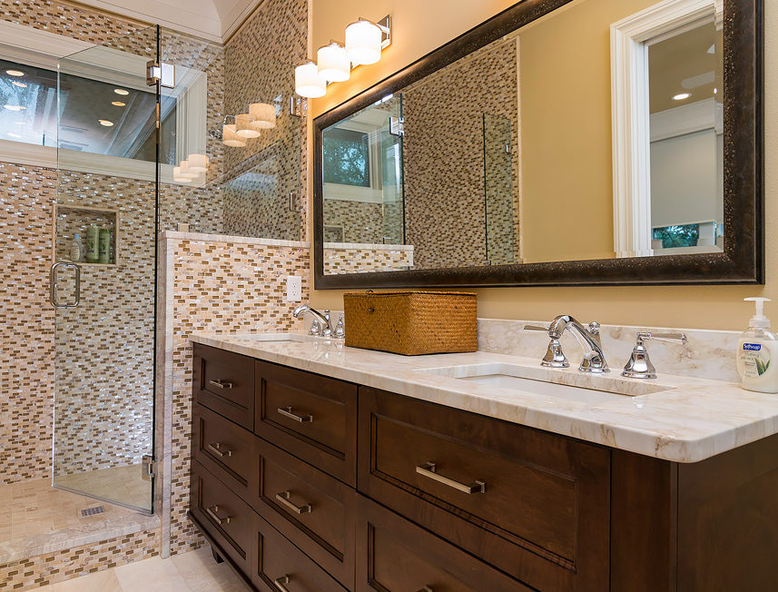Dark stained bathroom vanity with full overlay cabinetry and recessed panel drawer fronts