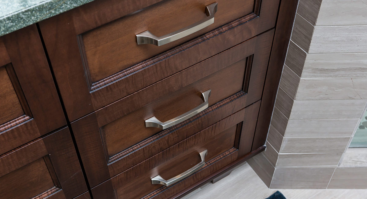 Dark stained full overlay cabinetry with recessed panel drawers