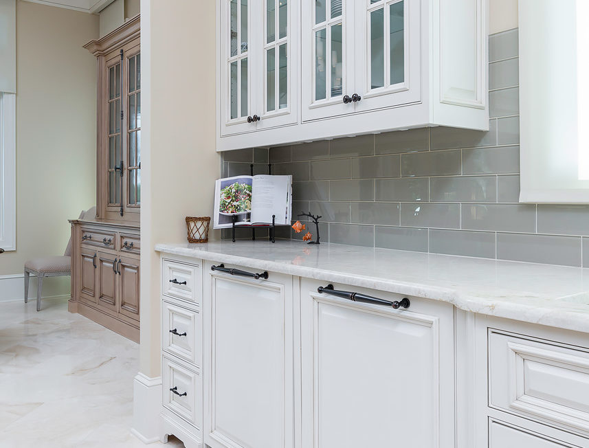 White kitchen cabinets featuring decorative upper mullion frame doors with glass inserts