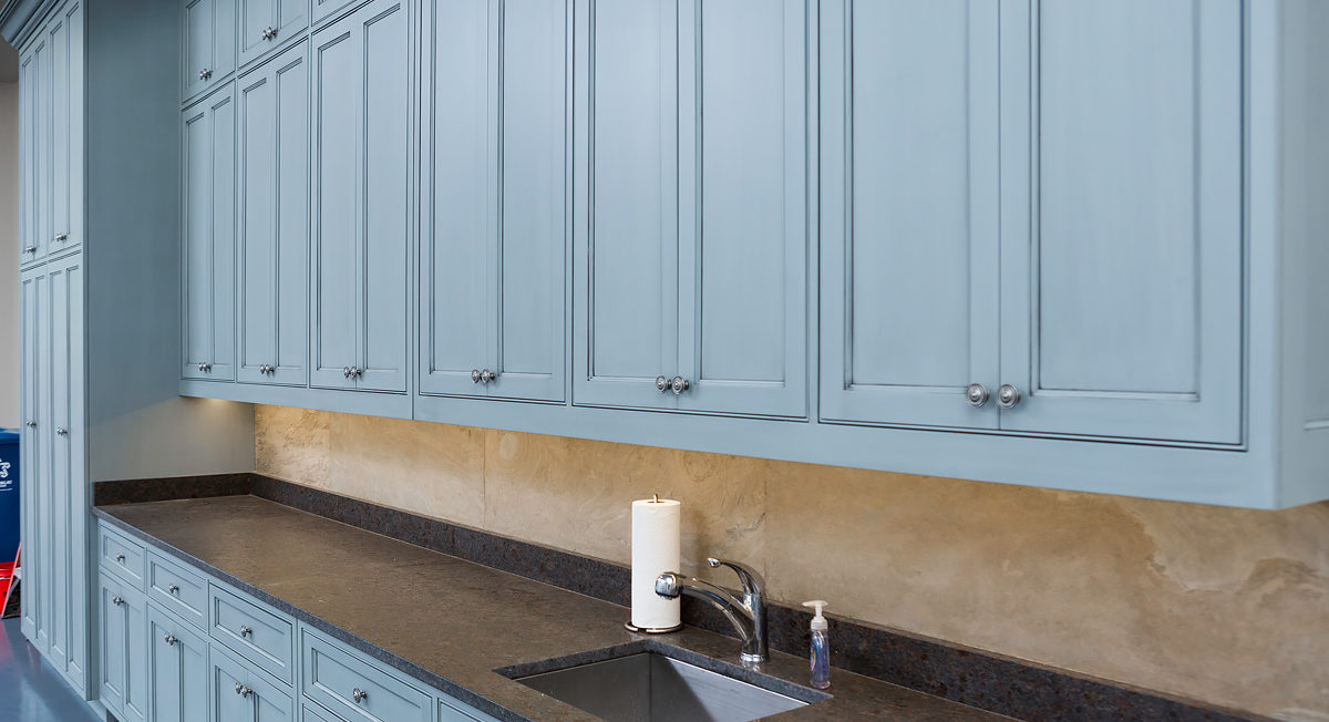 Blue garage storage cabinets with beaded inset cabinetry and recessed panel door and drawer fronts