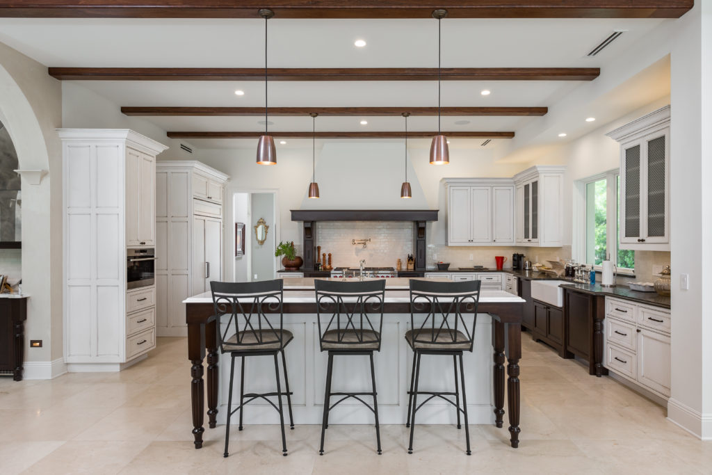 Tuscan Styled Kitchen with beaded inset cabinetry and recessed panel doors decorated with top knobs hardware