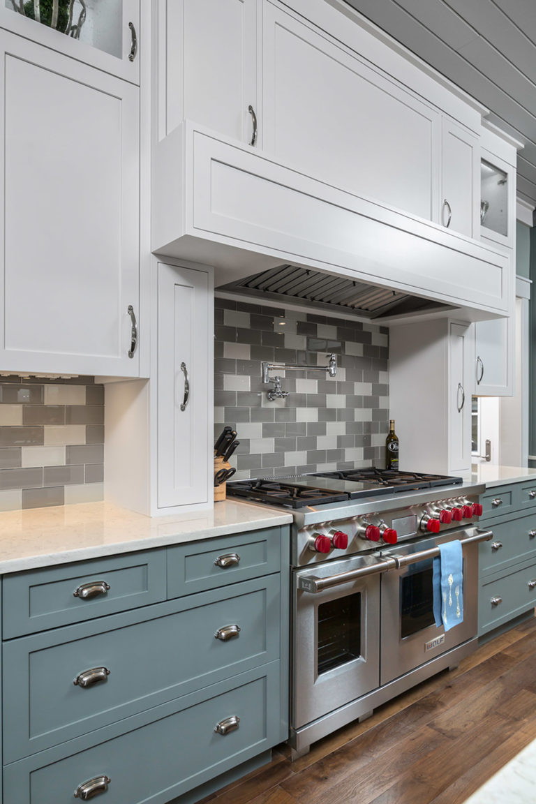 Custom Kitchen featuring inset shaker doors and drawers painted blue and a kitchen island in a barn wood worn finish. Decorative open frame doors on upper cabinets and open shelving for wine bottles.