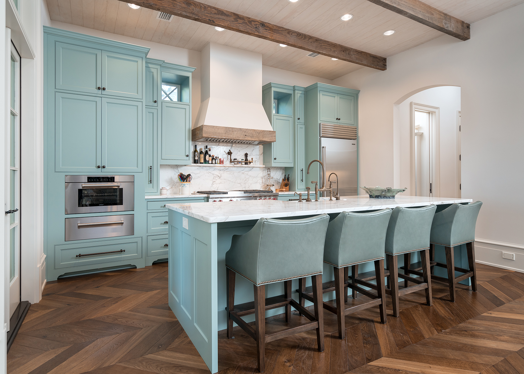 This custom kitchen has inset shaker doors painted a sea blue with specialty window cutouts framing the hood