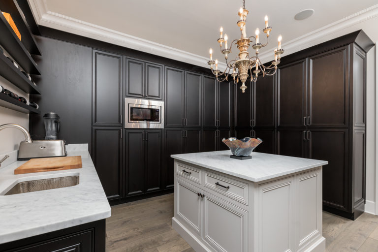 Custom built kitchen pantry featuring dark stained wood on inset cabinets with recessed doors. This pantry also features a white kitchen island with doors and drawers and all of the cabinetry is decorated with Top Knobs hardware