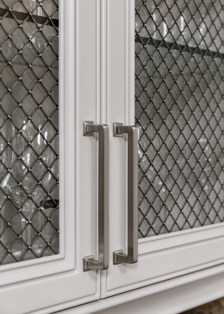 Details on the Top Knobs Ascendra pull in Brushed Satin Nickel on open framed doors with glass panels and decorative metal meshing overlay
