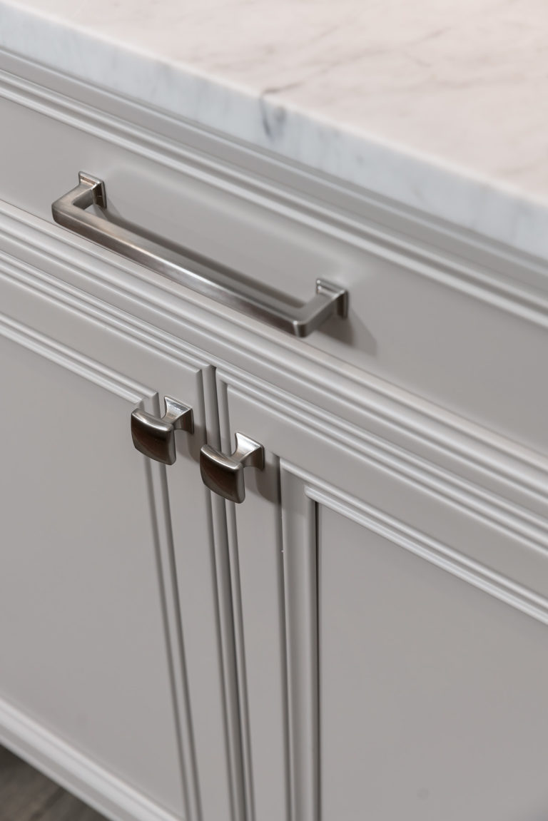 Top Knobs Ascendra Pull and Contour Knobs in Brushed Satin Nickel decorating off white inset cabinetry with recessed panels